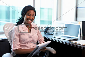 Portrait Of Female Doctor Working In Office