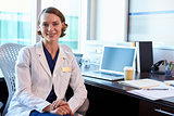 Portrait Of Female Doctor Wearing White Coat In Office