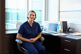 Portrait Of Nurse Wearing Scrubs Sitting At Desk In Office
