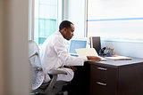 Doctor Wearing White Coat Reading Notes In Office