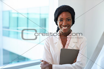 Portrait Of Female Doctor With Digital Tablet In Exam Room