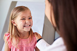 Pediatrician In White Coat With Child In Exam Room