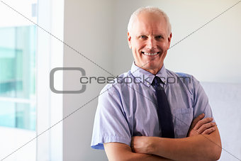 Portrait Of Male Doctor Standing In Exam Room