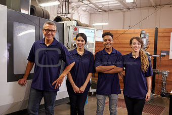 Portrait Of Engineer Training Apprentices On CNC Machine