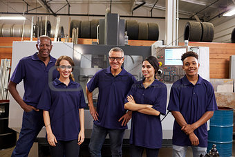 Portrait Of Engineers And Apprentices With CNC Machine