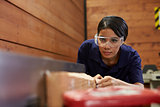 Female Carpenter Using Plane In Woodworking Woodshop