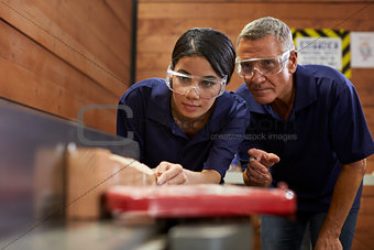 Carpenter Training Female Apprentice To Use Plane