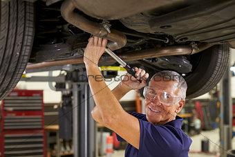 Portrait Of Auto Mechanic Working Underneath Car In Garage