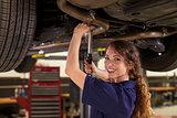 Portrait Of Female Auto Mechanic Working Underneath Car