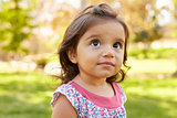 Mixed race Caucasian Asian toddler girl in a park, portrait