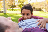 Mixed race boy lying in park with his white father, close up