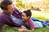 Mixed race Asian boy lying in a park with his white father