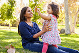 Asian Caucasian mixed race mother and young daughter in park