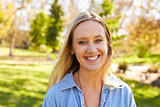Mid thirties white woman smiling to camera in a park