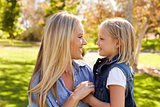 Blonde woman and her young daughter in a park side view