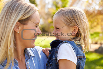 Blonde woman and young daughter look at each other, close up