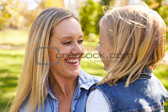 Blonde woman and young daughter laughing together, close up