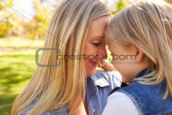 Blonde woman and her young daughter touching heads together