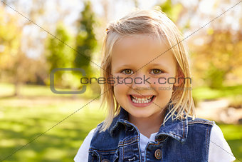 Five year old blonde girl in a park smiling to camera