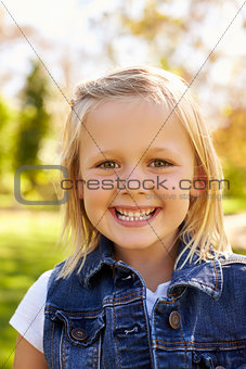 Five year old blonde girl in park smiles to camera, vertical