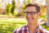 Middle aged white man wearing glasses looking away in a park