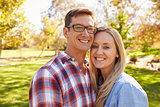 Adult Caucasian couple embracing in a park looking to camera