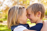Young brother and sister nose to nose in a park, side view
