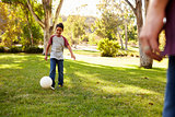 Seven year old boy playing football in a park with dad