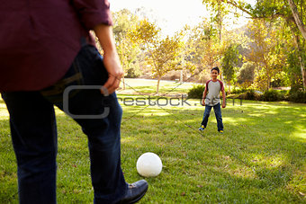 Dad kicking football to seven year old son in a park, crop