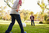 Seven year old boy kicking football to his dad in park, crop