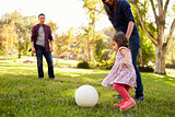 Parents kicking a ball with their young daughter in a park