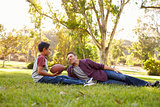Father and son with football relaxing in a park