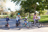 Young white family cycling together through a park