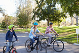 Parents and young son cycling together through a park