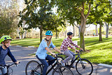 Parents and young son cycling through a park, close up