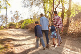 Young white family walking on a path in sunlight, back view