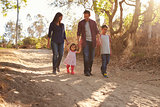 Mixed race family walking on rural path, front view