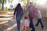 Mixed race family walking on rural path, backlit back view