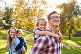 Parents carry kids piggyback in park, dad and girl in front