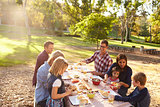 Two families having a picnic together at a table in a park