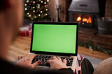 Man Using Laptop In Room Decorated For Christmas