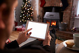 Man Using Digital Tablet In Room Decorated For Christmas