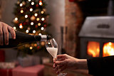 Couple Drinking Champagne In Room Decorated For Christmas