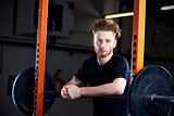 Portrait Of Young Man In Gym Lifting Weights On Barbell