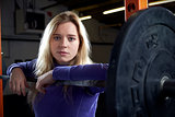 Portrait Of Young Woman In Gym Lifting Weights On Barbell