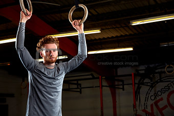Portrait Of Young Man In Gym With Olympic Rings