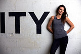 Woman Wearing Fitness Clothing Standing Against Wall Of Gym