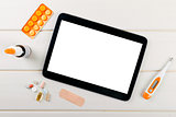 blank digital tablet with medical items on the table. top view