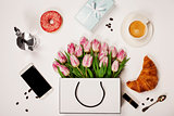 Top view of spring flowers, coffee, mobile phone, croissants,