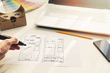 designer drawing website development wireframe on paper